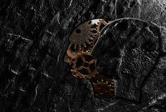 Stone head gears. Stone head cutout revealing gears on dark background Stock Image