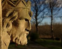 Stone head overlooking churchyard Stock Photography