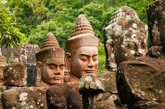 Stone Head Statues in Angkor Wat, Siem Reap, Cambodia, Indochina, Asia - oblique in colour. Newer and older stone heads in Angkor Wat, Cambodia, Indochina. The royalty free stock photos