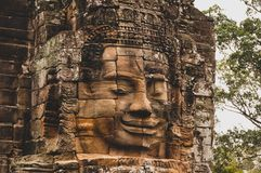 Weathered, Lichen-covered Stone Head Statue in Angkor Wat, Siem Reap, Cambodia, Indochina, Asia - face on in colour. Stone heads at different angles in Angkor stock images