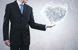 Stone heart. Businessman holding stone in shape of heart in palm Stock Image