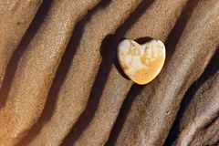Stone heart. Lies on the wavy sand of the beach. beautiful texture, suitable for decoration of the room, postcard. background for social posters royalty free stock image