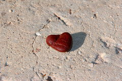 Stone in a shape of heart. A little stone of amazing and unusual form of heart looks brightly on grey asphalt Stock Image