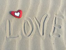 Stone heart and love word on the sand Stock Photos