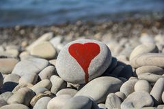 Stone heart painted with a red paint marker on the pebble as a gift for Saint Valentine day on the pebble background. I love you and stone heart painted with a royalty free stock photo