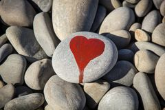 Stone heart painted with a red paint marker on the pebble as a gift for Saint Valentine day on the pebble background. I love you and stone heart painted with a stock photography