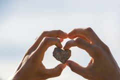 Stone with heart shape in the hand of a woman royalty free stock images