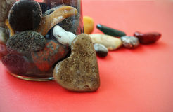 Stone heart and stones in the glass on red background. Stone heart on red background. Valentines Day background. Love card with heart shaped stone and sea stones Royalty Free Stock Images
