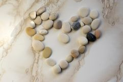 Stone heart, stones in the shape of a heart, happy valentines day, simplicity. Grey and white pebbles on marble background Royalty Free Stock Photos