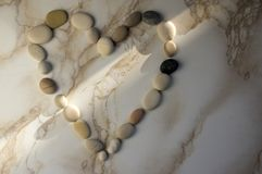 Stone heart, stones in the shape of a heart, happy valentines day, simplicity. Grey and white pebbles on marble background with sunlight line, romantic sign Royalty Free Stock Photos