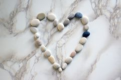 Stone heart, stones in the shape of a heart, happy valentines day, simplicity. Grey and white pebbles on marble background, romantic symbol Stock Photos