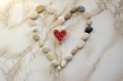 Stone heart, stones in the shape of a heart, happy valentines day, simplicity. Grey and white pebbles on marble background, red heart peg in center Stock Photos