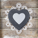 Stone heart on wooden background. Stone heart and lace on old wooden background Stock Images