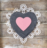 Stone heart on wooden background. Stone heart and lace on old wooden background Royalty Free Stock Image
