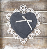 Stone heart on wooden background. Stone heart with ribbon and lace on wooden background Stock Images