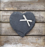 Stone heart on wooden background. Stone heart and ribbon on old wooden background Stock Photography