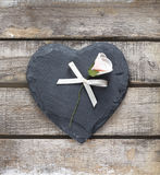 Stone heart on wooden background. Stone heart and rose on old wooden background Stock Images