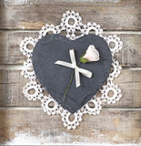 Stone heart on wooden background. Stone heart with rose on old wooden background Stock Photo