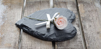 Stone heart on wooden background. Stone heart and rose on old wooden background Stock Photo