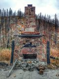 Stone Hearth And Chimney After A Wildfire. The stone hearth and chimney is all that is left after a devastating wildfire burned the cabin and the surrounding stock photo