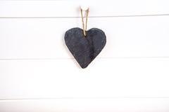 Stone hearth shape sign hanging on door. Black stone slate herath shape blank sign hanging on white wooden door stock photo