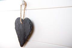 Stone hearth shape sign hanging on door. Black stone slate herath shape blank sign hanging on white wooden door stock photos