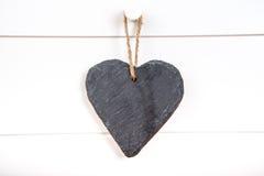 Stone hearth shape sign hanging on door. Black stone slate herath shape blank sign hanging on white wooden door royalty free stock photos