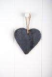 Stone hearth shape sign hanging on door. Black stone slate herath shape blank sign hanging on white wooden door Stock Photography