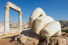 Stone Hercules hand at the antique Citadel in Amman, Jordan. At the background: ruins of the Hercules temple and Amman city Royalty Free Stock Photo