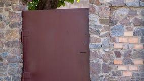 Stone high fence Brown steel door close up