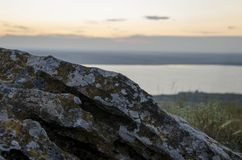 A stone on a high mountain. Sunset. Stone on the background of a sunset at a mountain lake. Background for text stock photography