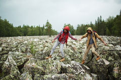 Stone hiking. Young tourists walking down big stones while hiking Royalty Free Stock Photo