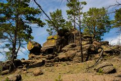 Stone hill in the forest. big rocks in the woods. the mountain of rocks around the pine trees. Big rocks in the woods. a mountain of stones in the forest around royalty free stock photography