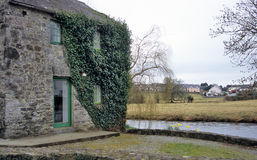Stone House. An old stone house sits by a river in an Irish village stock images