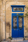 Stone house with a blue gate, island Malta. Wall of a stone building in the capital of Malta - Valletta. Bright blue wooden gate with two glasses with a Stock Photo