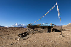 Stone house with colored flags on a background of mountains, Himalayas, Nepal Royalty Free Stock Image