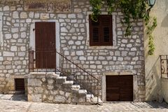 Stone house, Krk, Croatia. View from the street on a house made of white stones. Brown wooden doors and shutter on the window. City Krk, island Krk, Croatia Royalty Free Stock Photos