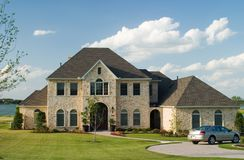 Stone House on Lake. Very large and beautiful stone and brick house on a small lake with generic car in front circle drive and white puffy clouds in the sky stock image