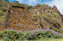 Stone house and lavender at foot of rocky mountain Royalty Free Stock Image