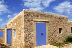 Stone house masonry blue sky door windows Stock Images