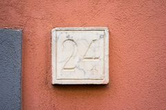 Stone house number 24. House number twenty four24 carved in stone on a plastered wall Stock Photos