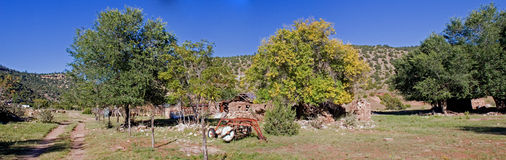 Stone house panorama 2. A true wide panorama of an old stone farmhouse, collapsed, farm implements in front and and stone walls of the outbuildings to the side Royalty Free Stock Image