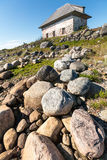 Stone house on the rocky shore. Stock Photography