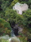 A stone house without a roof stands on the edge of a high cliff above the river amidst the abundant greenery of the forest. Stone house without a roof stands on Royalty Free Stock Photo