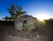 Stone house at sunset with tree Stock Photography