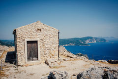 Stone house on the top of the sea island hill. Old stone house with dark wooden door high on the mountain overlooking the Mediterranean sea. Corfu island in stock photography