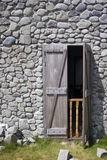 Stone house, wooden door. A stone house with it's wooden door left ajar royalty free stock image