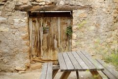 Stone house with wooden door next to a wooden table stock photography