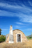 Stone hut - vertical. Strange stone hut against blue sky with white clouds royalty free stock images