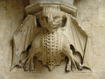Stone imp carving on wall. Stone carving of imp on wall of church stock photo